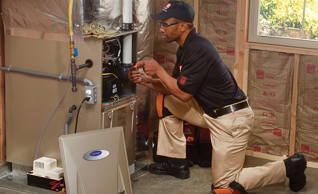 A person removes the front panel of a furnace to check the pilot light.