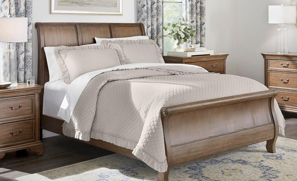 Một chiếc giường được làm bằng chăn bông màu nâu nhạt.
