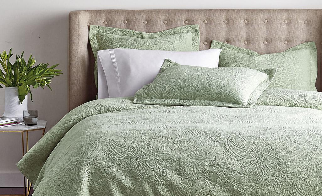 Giường làm bằng khăn phủ matelasse màu xanh lá cây