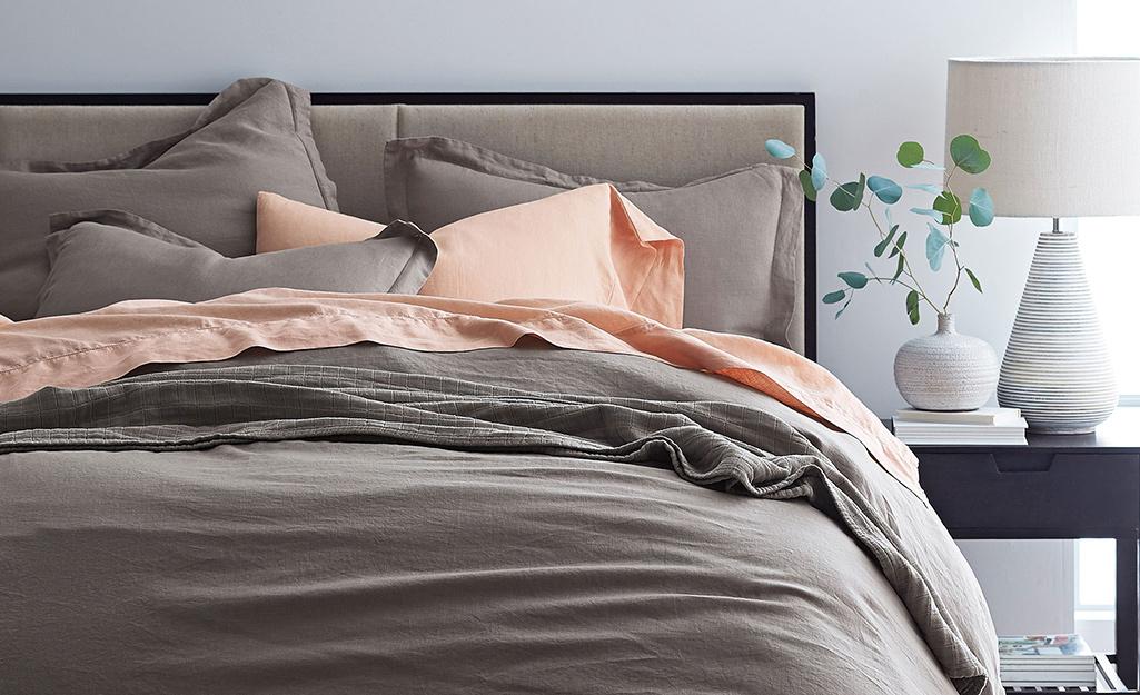 Một chiếc giường trải bộ khăn trải giường màu nâu nhạt.
