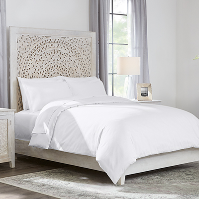 A bed made with lightweight, white bedding