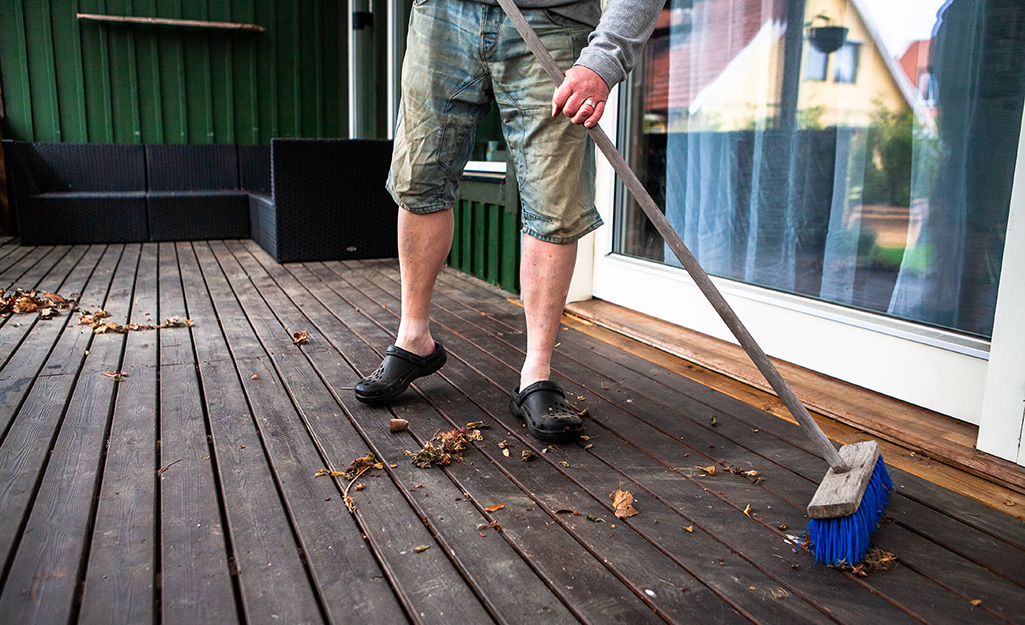 A person sweeps a deck with a push broom.