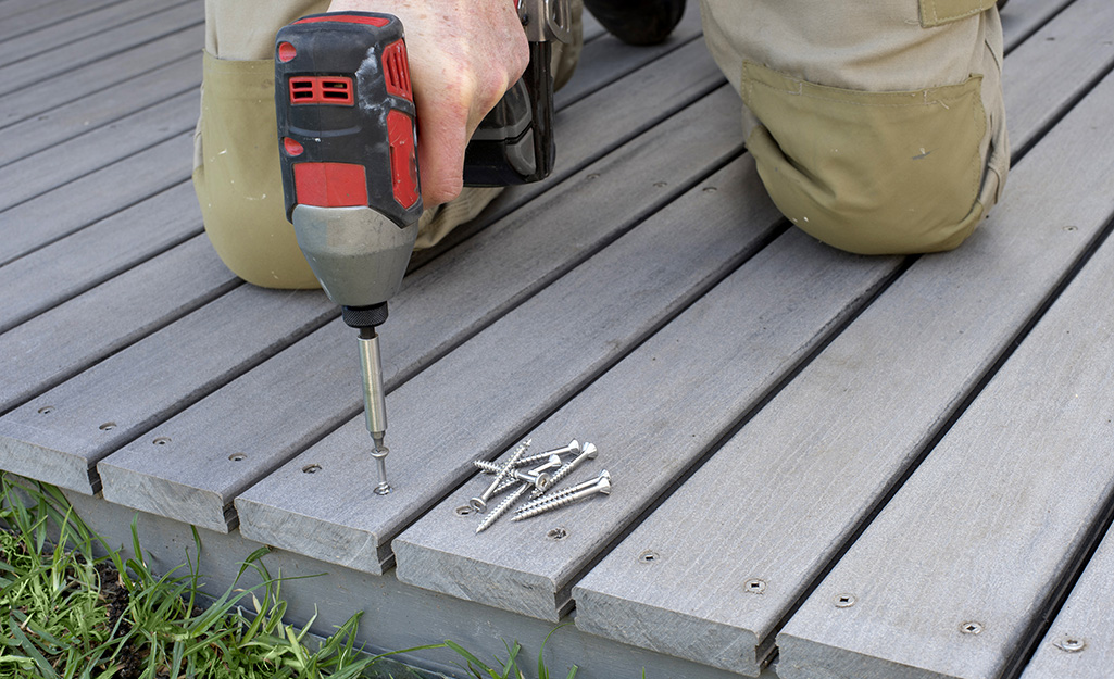 A person drives wood screws into a deck board with a power driver.