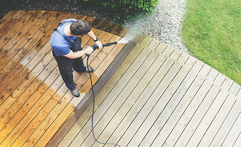 A person cleans a deck with a pressure washer.