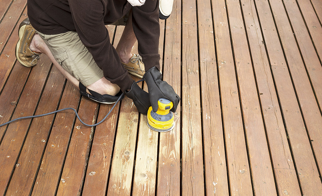 A person sands a deck with an orbital sander.