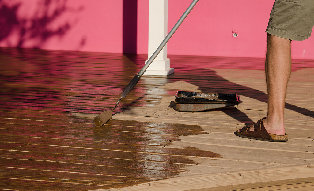 A person applies stain to a deck with a roller.