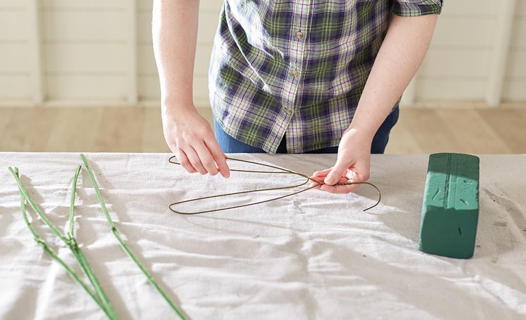 A person bending a coat hanger into a new shape.