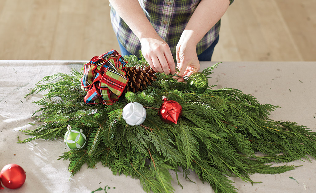 Someone arranging a Christmas wreath.