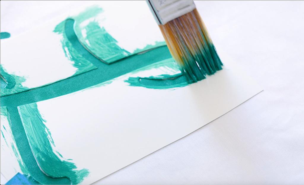 Một người sử dụng cọ vẽ, bút chì và sơn màu xanh lá cây để vẽ một chữ lồng.