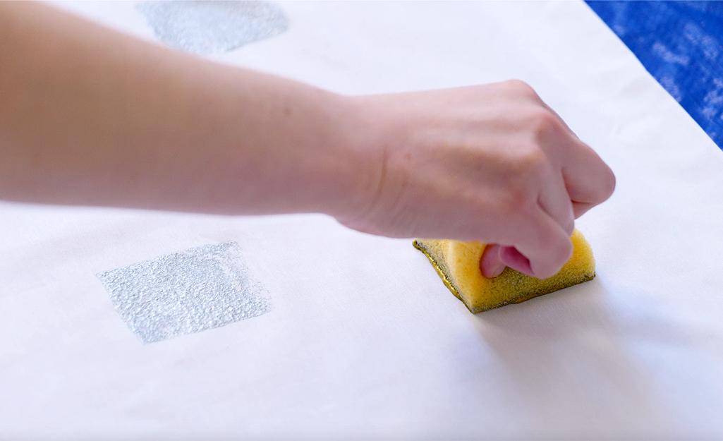 Một người sử dụng một miếng bọt biển để đóng dấu sơn lên áo gối.