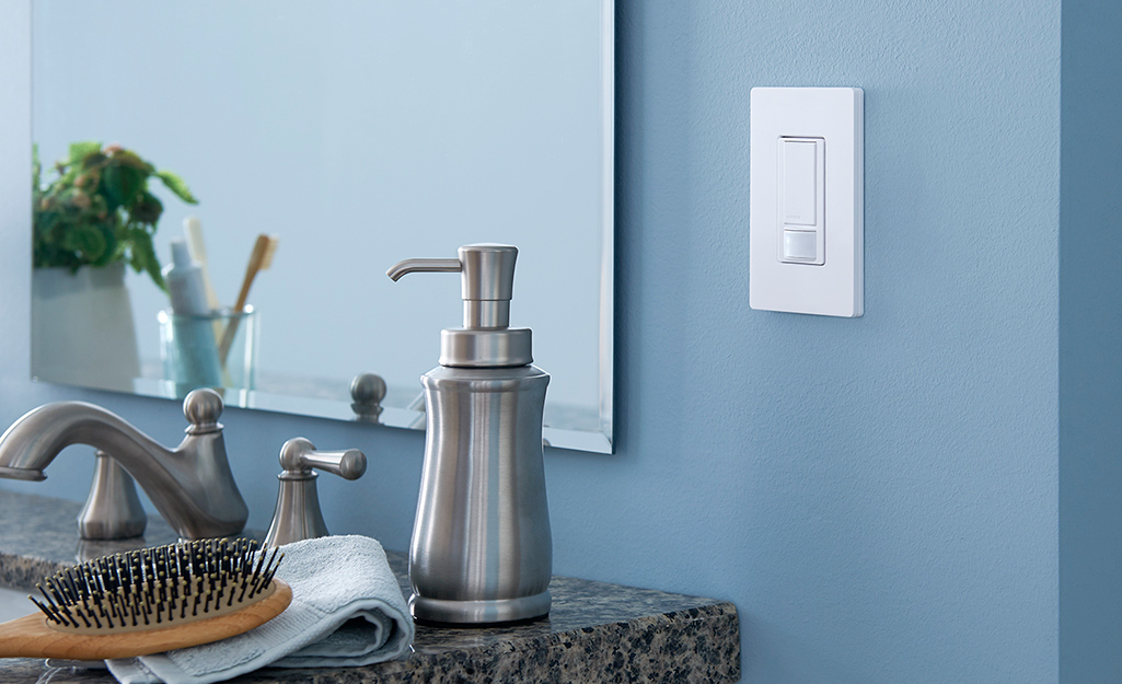 A motion detecting light switch next to a bathroom sink.