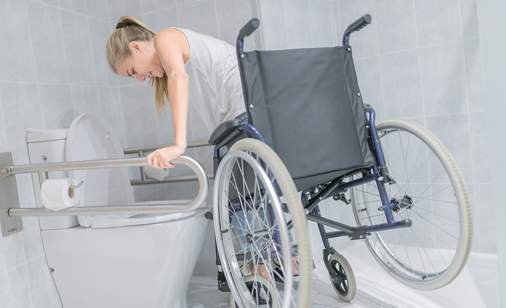 A person using grab bars to transfer from a wheelchair to a toilet.