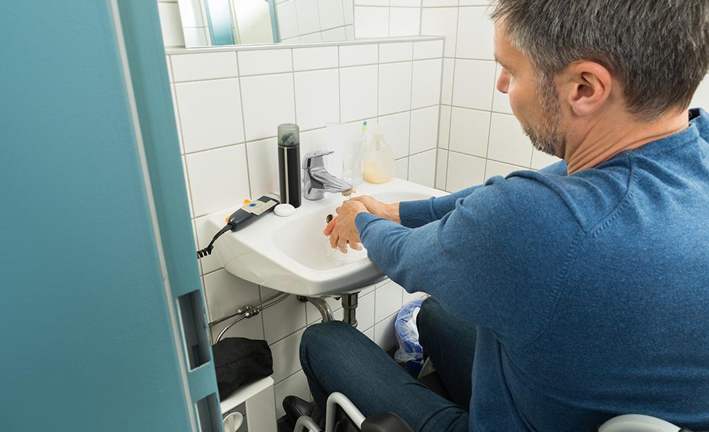 A person in a wheelchair using a bathroom sink.