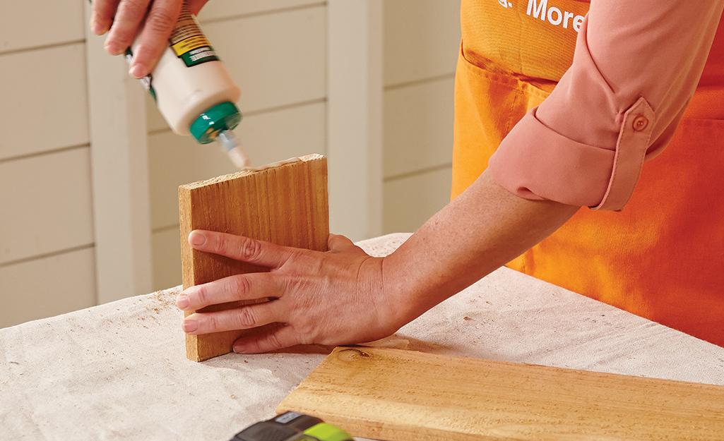 Một người bôi keo dán gỗ vào mặt của tấm ván gỗ hình vuông.