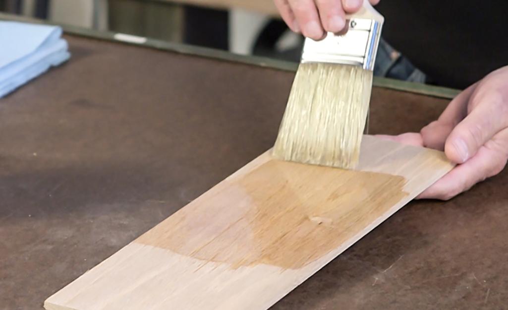 Một người sơn một lớp hoàn thiện bằng gỗ trong suốt lên tấm ván gỗ đã được chà nhám bằng chổi sơn.