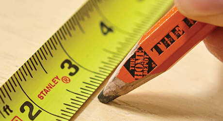 Someone marking a measurement on wood using a tape measure.