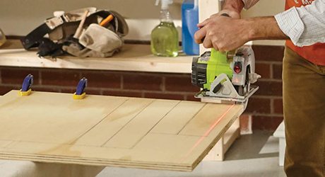 Person using a circular saw to cut a plywood board