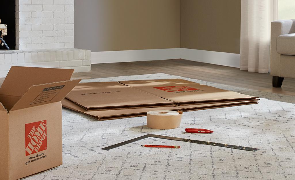 Các loại hộp di chuyển, dụng cụ đo lường và băng dính trên sàn.