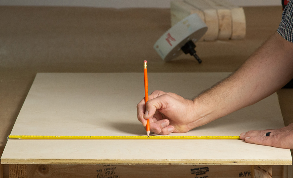 A plywood board being measured for a cornhole top.