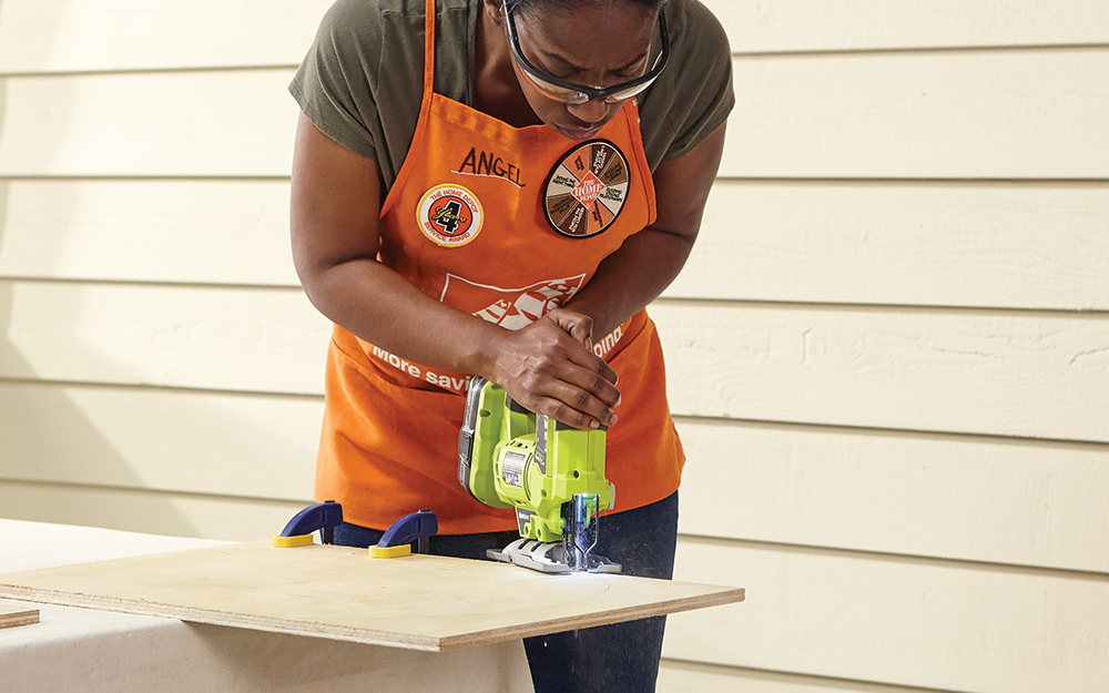 A woman using a jigsaw to cut into plywood