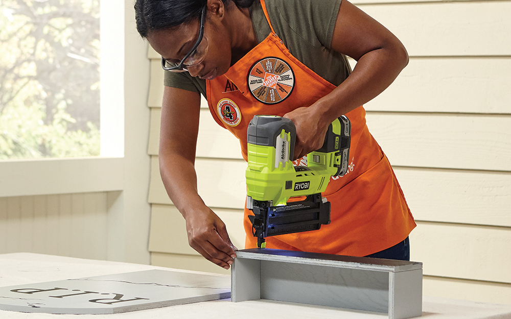 A woman using a nailer to attach the box bottom