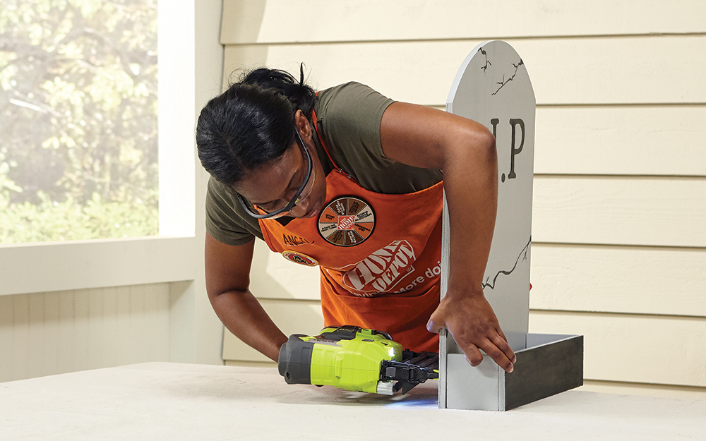 A woman using a nailer to attach the box sides