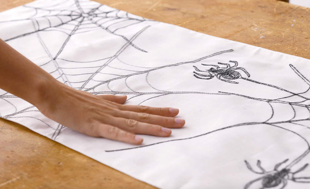 A hand smooths out a Halloween themed table runner.