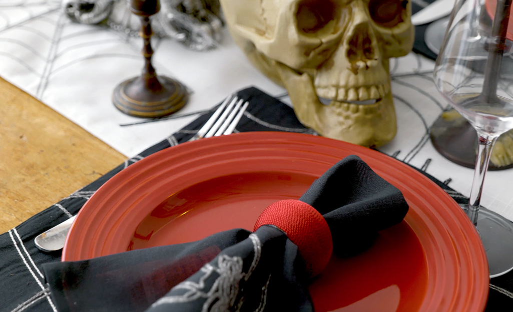 A black napkin with a red napkin ring sits atop a red plate.