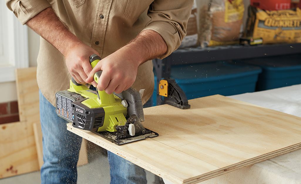 Someone using a circular saw to cut a sheet of plywood.