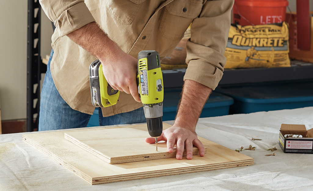 Someone using a drill to fasten together two pieces of plywood.