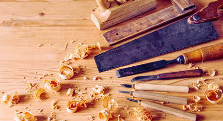 Collection of woodworking tools lying on top of a wood surface.