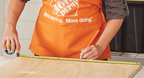 A person measuring a section of wood.