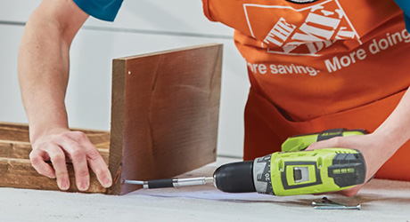 A person using a drill driver to attach two boards together.