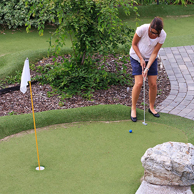 A woman golfing on a putting green made of synthetic turf.