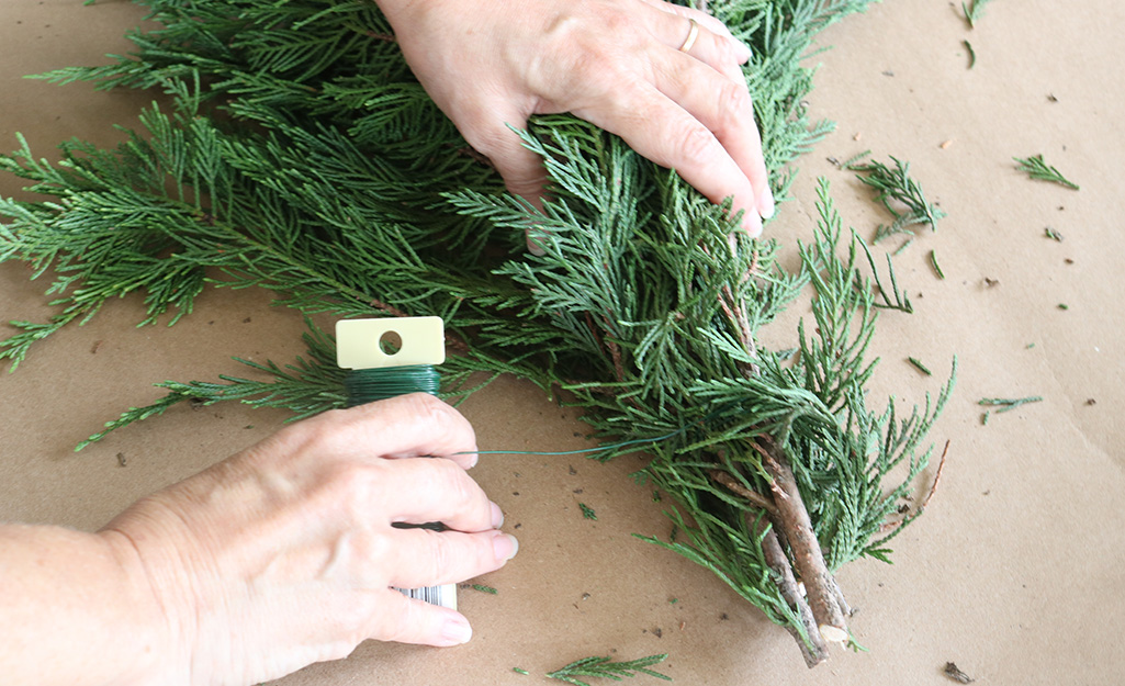 A person bundling pine branches together with floral wire.