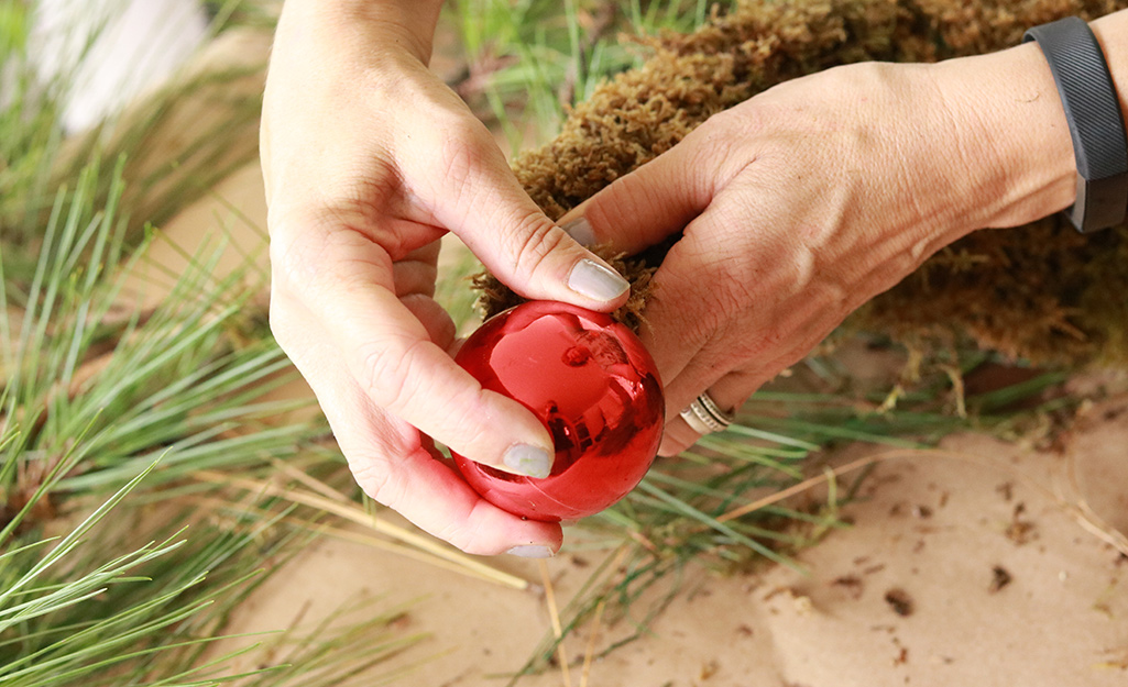 A person attaching a red ornament to the end of the moss hat.