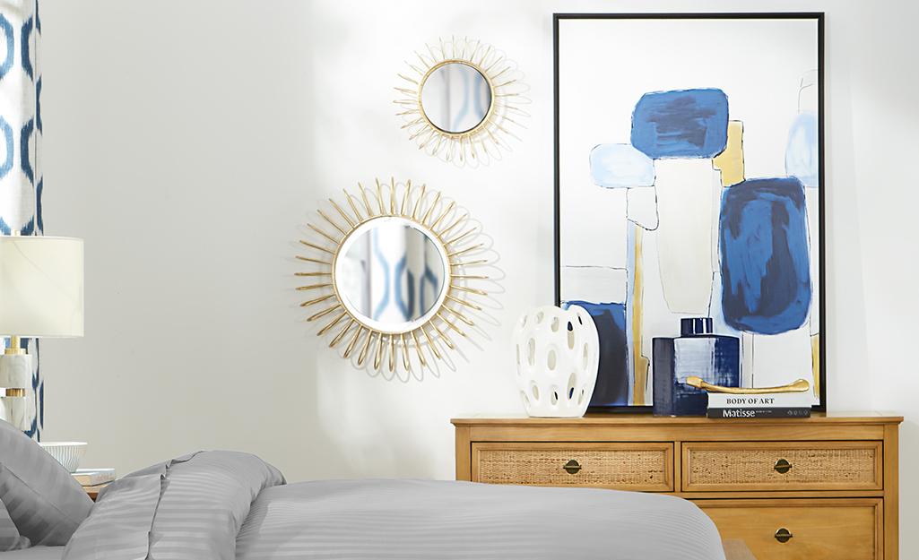 Một phòng ngủ với gương tròn và tác phẩm nghệ thuật trên tường.