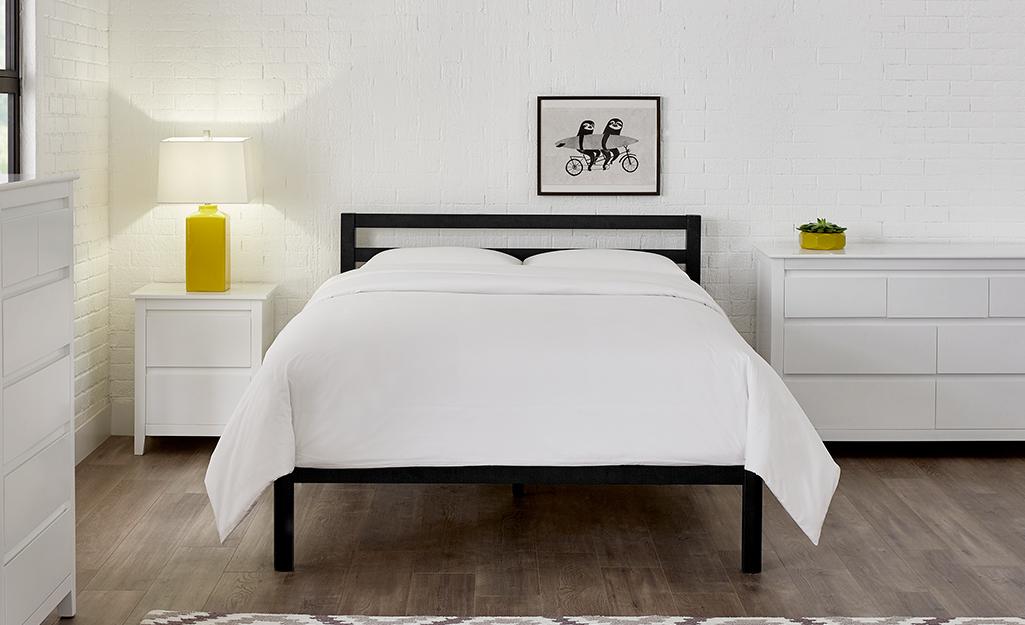 Phòng ngủ với đồ nội thất và giường màu trắng.