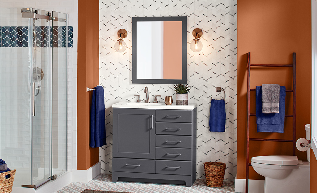 Phòng tắm với bàn trang điểm màu xám và cửa vòi hoa sen trong suốt.
