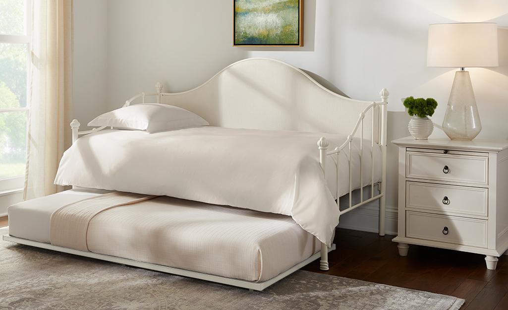 Một chiếc giường có bánh xe màu trắng trong phòng ngủ.