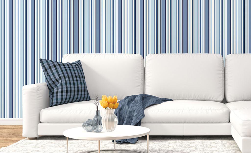 Phòng khách với những bức tường sọc xanh và ghế sofa trắng.