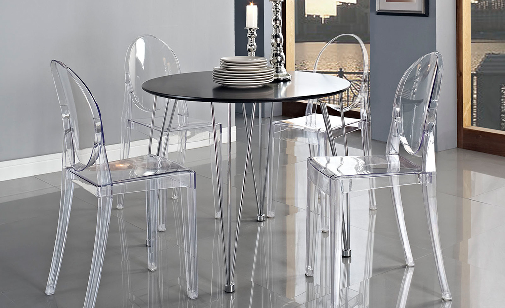 Một bộ ăn uống với những chiếc ghế màu trắng trong suốt.