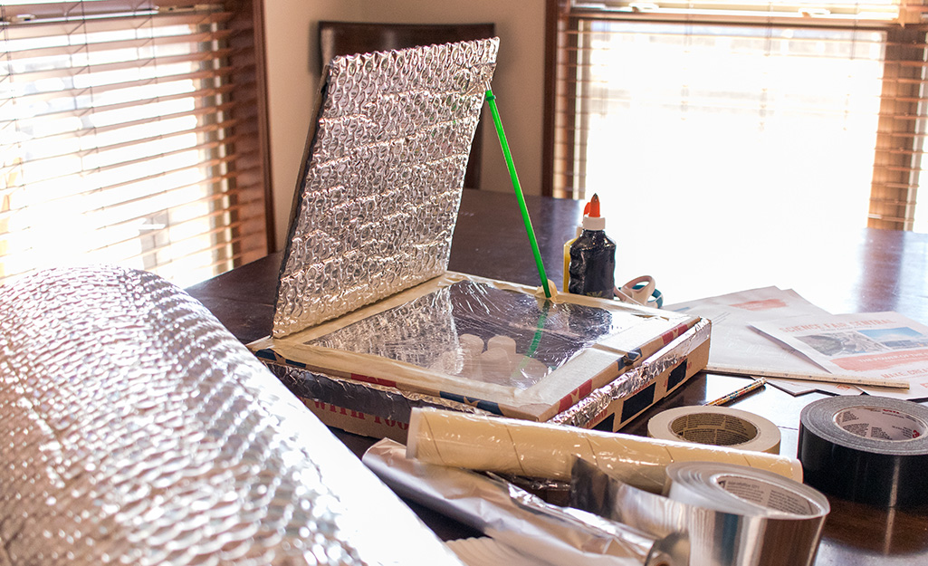 A homemade solar oven surrounded tape, glue and other craft supplies.