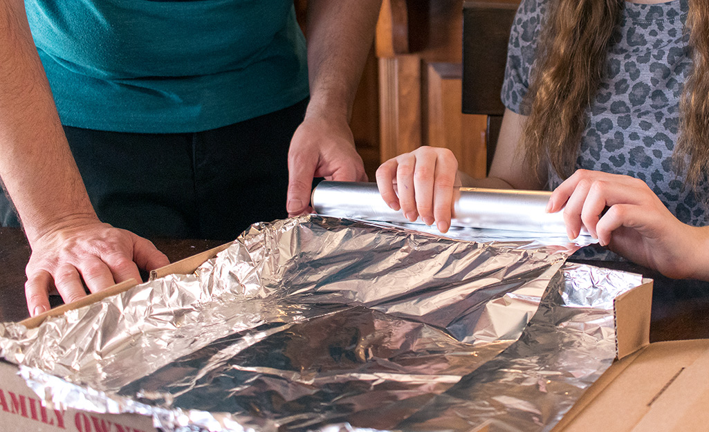 A girl unrolling foil into an open pizza box.