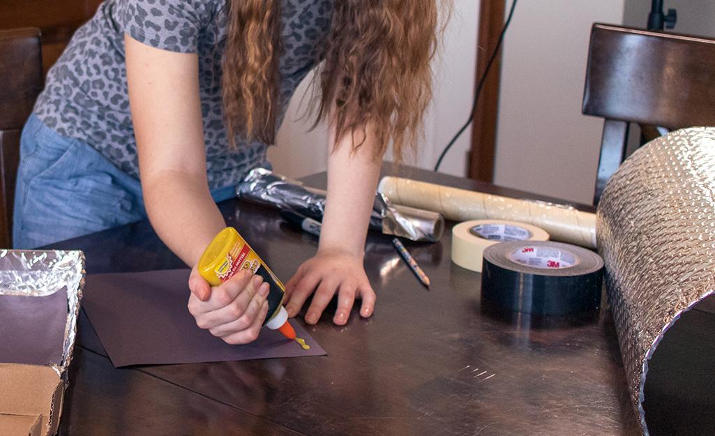 A girl applying glue to cardboard paper.