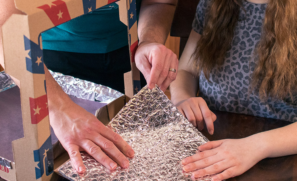 Two people adjusting foil in a pizza box.