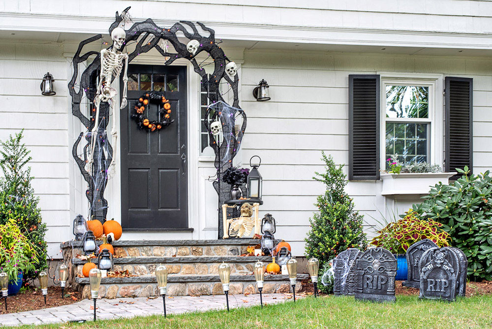 A front door and yard with Halloween decorations