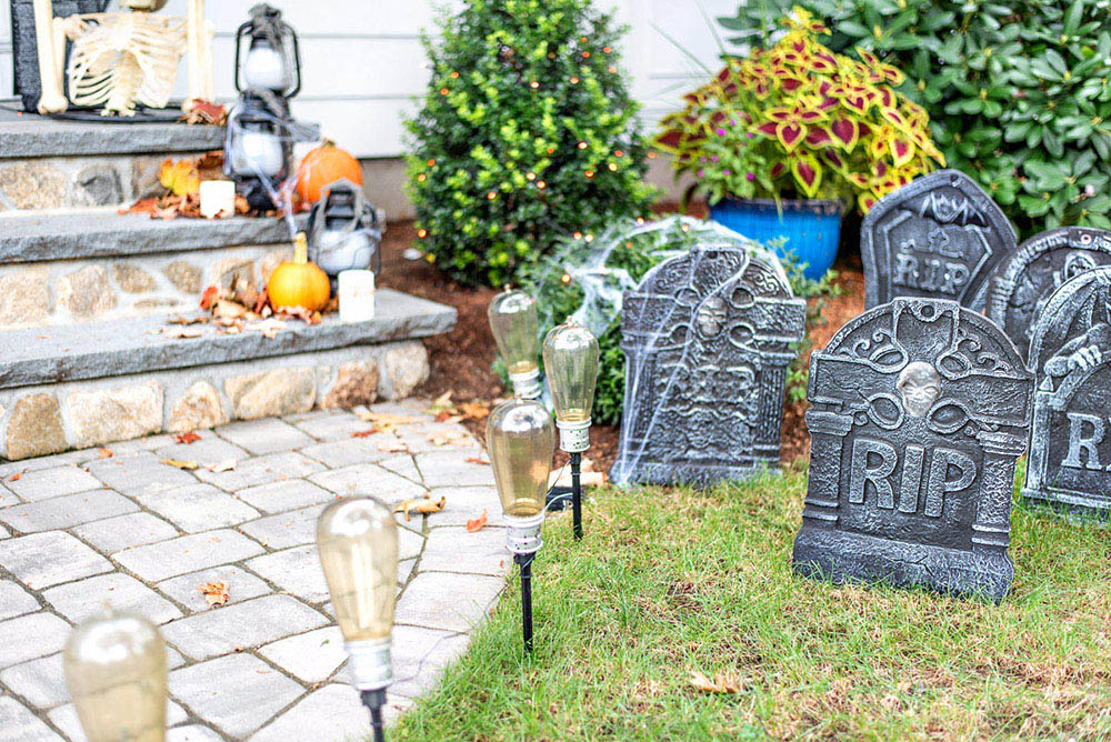 A close shot of decorative tombstones and pathway light leading to steps