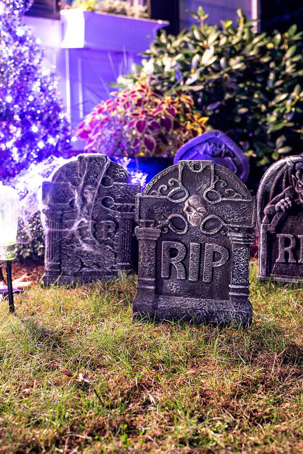 A night shot of the decorative tombstone with purple lights
