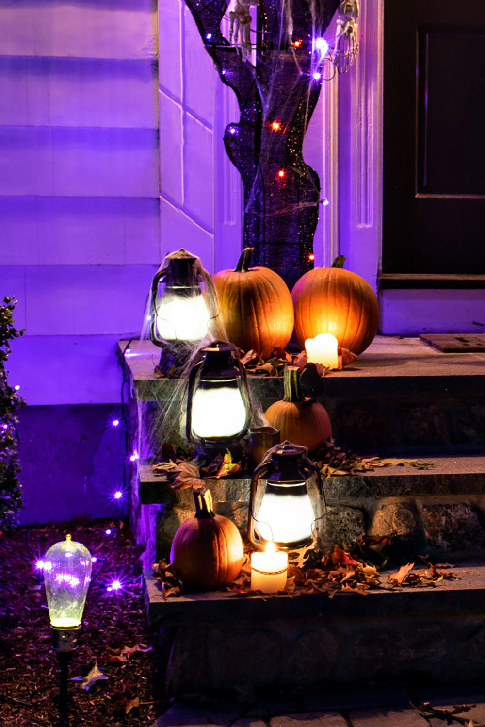 A night view of the lanterns and pumpkins on the front steps